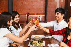 Grupp av asiatisk lyckliga och le ung man och kvinnor som rymmer en alkoholiserad coctail för att rosta och att fira i socialt pa arkivfoton