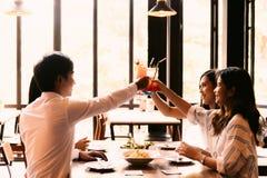 Grupp av asiatisk lyckliga och le ung man och kvinnor som rymmer en alkoholiserad coctail för att rosta i restaurang mot solnedgå royaltyfri fotografi