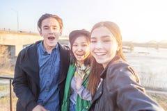 Grupp av asiatisk ton?r som tar selfie p? telefonen och att ha gyckel, b?sta v?n och digitalt utvecklingsbegrepp royaltyfri bild