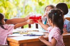 Grupp av asiatiska barn som klirrar exponeringsglas av rött fruktsaftvatten Arkivbilder