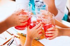 Grupp av asiatiska barn som klirrar exponeringsglas av rött fruktsaftvatten Royaltyfri Fotografi