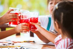 Grupp av asiatiska barn som klirrar exponeringsglas av rött fruktsaftvatten Arkivfoto