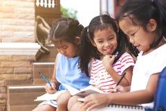 Grupp av asiatiska barn som läser en bok royaltyfria bilder