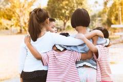 Grupp av asiatiska barn som tillsammans kramar och spelar Royaltyfri Bild
