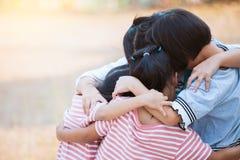 Grupp av asiatiska barn som tillsammans kramar och spelar Royaltyfri Foto