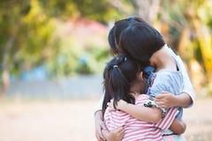 Grupp av asiatiska barn som tillsammans kramar och spelar Arkivbild