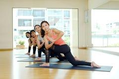 Grupp av asiatiska kvinnor som utbildar inomhus grupp för yoga i namastepostu royaltyfri bild