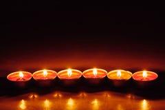 Grupp av att bränna röda tealightstearinljus Arkivfoton