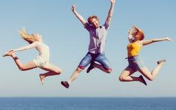 Grupp av att hoppa för flickor för vänpojke som två är utomhus- Arkivfoton