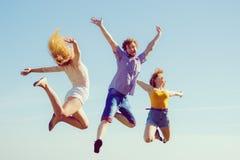 Grupp av att hoppa för flickor för vänpojke som två är utomhus- Royaltyfri Foto