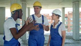 Grupp av att le byggmästare i hardhats som talar på konstruktionsplatsen arkivfilmer