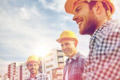 Grupp av att le byggmästare i hardhats utomhus royaltyfria foton