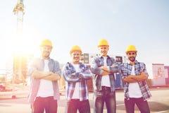 Grupp av att le byggmästare i hardhats utomhus Royaltyfri Foto