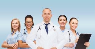 Grupp av att le doktorer med skrivplattan royaltyfri foto