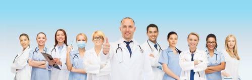 Grupp av att le doktorer med visningtummar upp royaltyfri bild