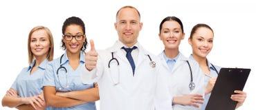 Grupp av att le doktorer med visningtummar upp arkivfoto