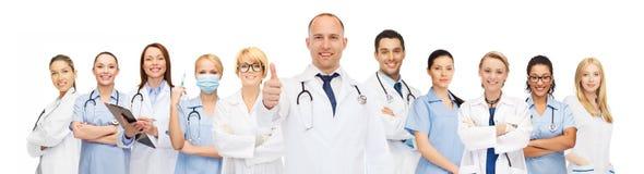 Grupp av att le doktorer med visningtummar upp royaltyfria bilder