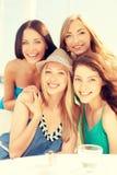 Grupp av att le flickor i kafé på stranden Royaltyfri Foto