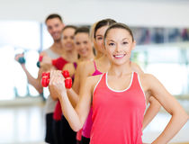 Grupp av att le folk med hantlar i idrottshallen Royaltyfri Bild