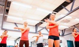Grupp av att le folk som sträcker i idrottshallen Royaltyfri Fotografi