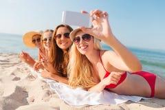 Grupp av att le kvinnor med smartphonen på stranden Royaltyfri Foto