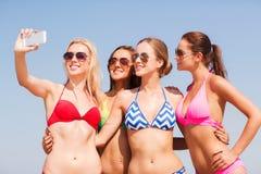 Grupp av att le kvinnor som gör selfie på stranden Royaltyfri Bild