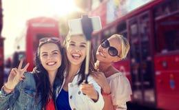 Grupp av att le kvinnor som tar selfie i london royaltyfri fotografi