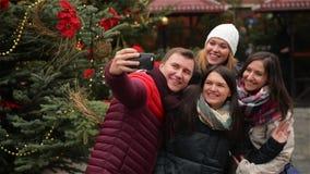Grupp av att le mannen och kvinnor som utomhus tar Selfie nära Xmas-träd Vänner som har gyckel på julmarknaden glatt stock video