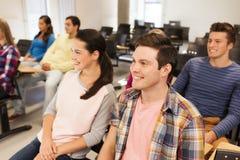 Grupp av att le studenter i hörsal Arkivfoto