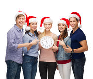 Grupp av att le studenter med klockan som visar 12 Royaltyfri Foto