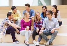 Grupp av att le studenter med pappers- kaffekoppar Fotografering för Bildbyråer