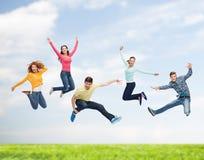 Grupp av att le tonåringar som hoppar i luft Royaltyfri Fotografi