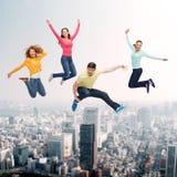 Grupp av att le tonåringar som hoppar i luft Fotografering för Bildbyråer