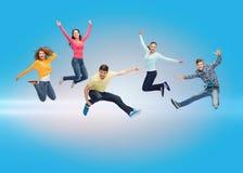 Grupp av att le tonåringar som hoppar i luft Arkivfoto