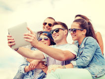 Grupp av att le tonåringar som ser minnestavlaPC Royaltyfria Foton