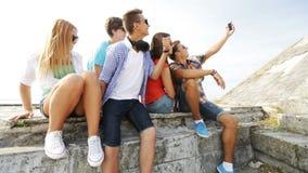 Grupp av att le tonåringar som utomhus gör selfie stock video