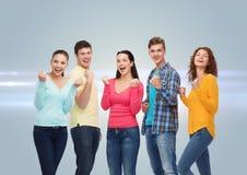 Grupp av att le tonåringar som visar triumfgest Arkivbild