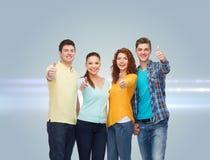 Grupp av att le tonåringar som visar upp tummar Arkivfoto