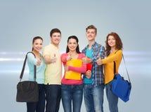 Grupp av att le tonåringar som visar upp tummar Arkivbilder