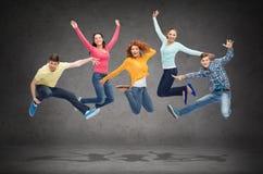 Grupp av att le tonåringar som hoppar i luft Royaltyfria Foton