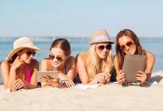 Grupp av att le unga kvinnor med minnestavlor på stranden Royaltyfri Bild
