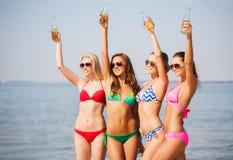 Grupp av att le unga kvinnor som dricker på stranden Royaltyfri Fotografi