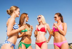 Grupp av att le unga kvinnor som dricker på stranden Royaltyfria Foton