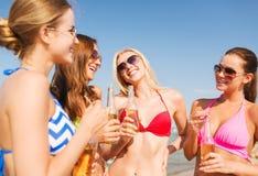 Grupp av att le unga kvinnor som dricker på stranden Arkivfoto