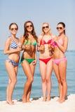 Grupp av att le unga kvinnor som dricker på stranden Royaltyfri Bild