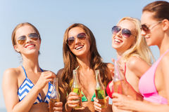 Grupp av att le unga kvinnor som dricker på stranden Royaltyfri Foto