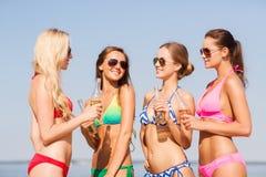 Grupp av att le unga kvinnor som dricker på stranden Arkivbilder
