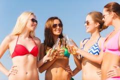 Grupp av att le unga kvinnor som dricker på stranden Arkivfoton
