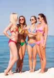 Grupp av att le unga kvinnor som dricker på stranden Fotografering för Bildbyråer
