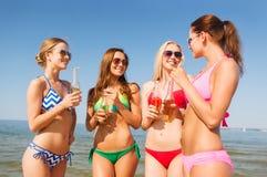 Grupp av att le unga kvinnor som dricker på stranden Royaltyfria Bilder